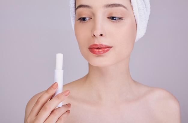 Jovem mulher aplicar protetor labial no fundo.