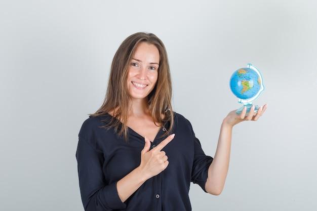 Jovem mulher apontando o dedo para o globo em uma camisa preta e parecendo feliz