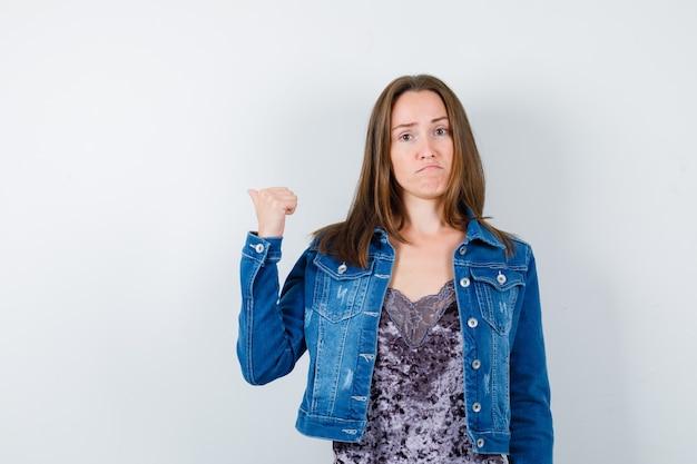 Jovem mulher apontando o polegar para trás em jaqueta jeans, vestido e parecendo insatisfeita, vista frontal.