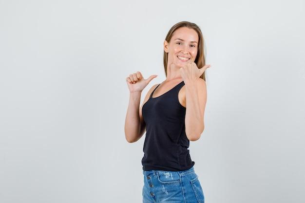 Jovem mulher apontando os polegares para trás em camiseta, shorts e olhando alegre.