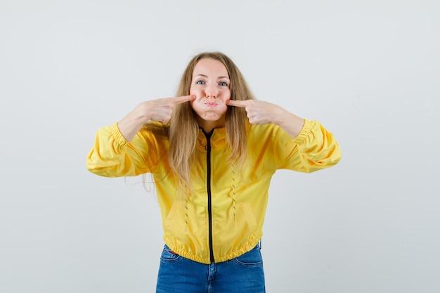 Jovem mulher apontando para a boca com o dedo indicador e bochechas infladas em uma jaqueta amarela e jeans azul e olhando otimista, vista frontal.