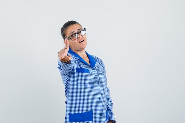 Jovem mulher apontando para a câmera com o dedo indicador e usando óculos na camisa de pijama azul guingão e bonita, vista frontal.