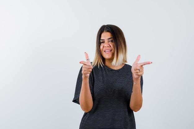 Jovem mulher apontando para a câmera com o dedo indicador em um vestido preto e olhando feliz, vista frontal.