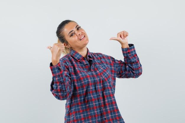 Jovem mulher apontando para a esquerda com os dois dedos indicadores em uma camisa xadrez e parecendo feliz. vista frontal.