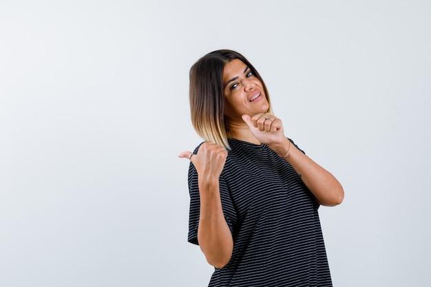 Jovem mulher apontando para a esquerda com os polegares em um vestido preto e olhando feliz, vista frontal.