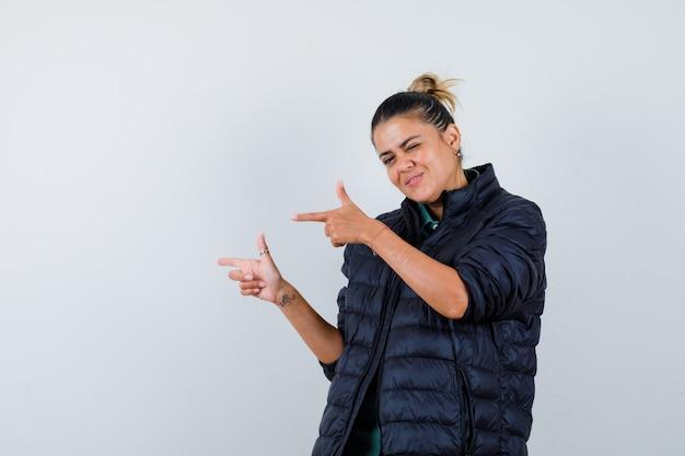 Jovem mulher apontando para a esquerda com uma jaqueta de baiacu e parecendo alegre. vista frontal.