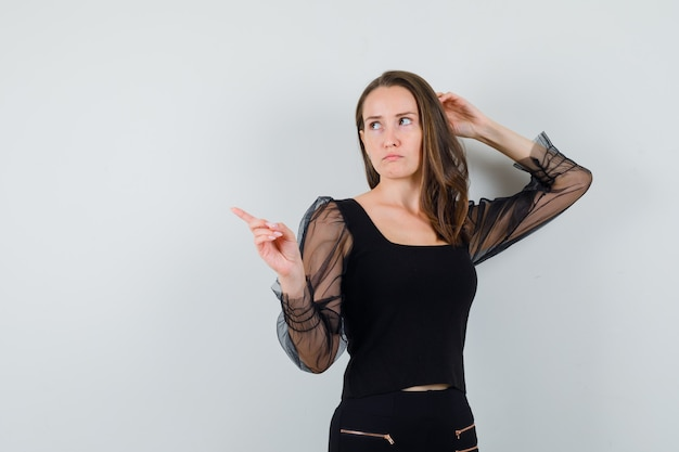 Jovem mulher apontando para a esquerda e pensando em algo em blusa preta e calça preta e parecendo pensativa. vista frontal.