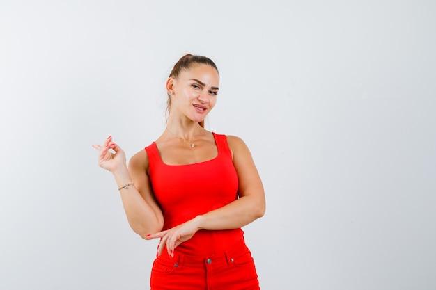 Jovem mulher apontando para cima em um top vermelho, calças e olhando pensativo, vista frontal.