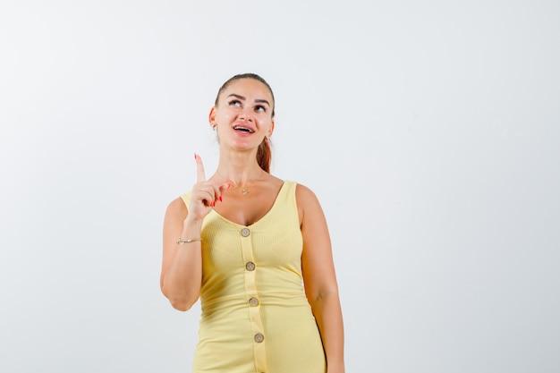 Jovem mulher apontando para cima em um vestido amarelo e olhando curiosa, vista frontal.
