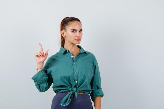 Jovem mulher apontando para cima em uma camisa verde e olhando cuidadosa, vista frontal.