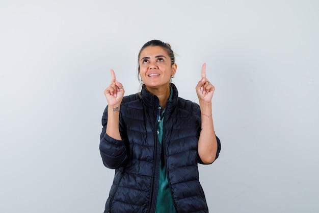 Jovem mulher apontando para cima, olhando para cima com uma jaqueta inflável e parecendo alegre. vista frontal.