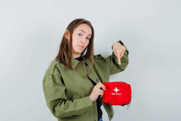 Jovem mulher apontando para dentro do kit de primeiros socorros com jaqueta verde, vista frontal.