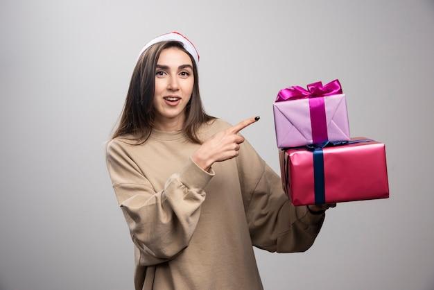 Jovem mulher apontando para duas caixas de presentes de natal.