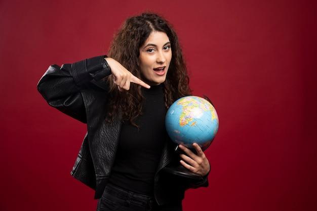 Jovem mulher apontando para o globo.