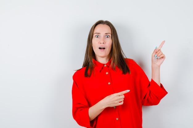Jovem mulher apontando para o lado e para cima com uma blusa vermelha e parecendo chocada, vista frontal.