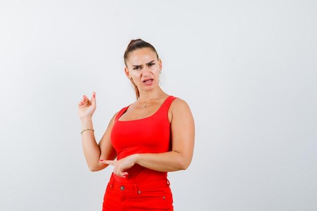 Jovem mulher apontando para o lado e para cima em uma blusa vermelha, calça e parecendo confusa, vista frontal.