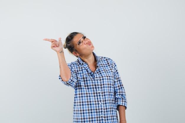 Jovem mulher apontando para o lado enquanto faz beicinho com os lábios na camisa quadriculada e parece estranho.