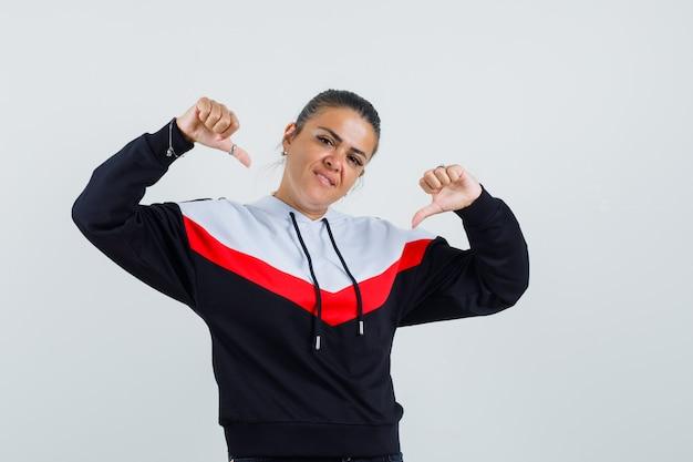 Jovem mulher apontando para si mesma com os dedos indicadores em suéter e calça jeans preta e bonita, vista frontal.