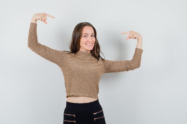 Jovem mulher apontando para si mesma em um suéter dourado dourado e calças pretas e parecendo feliz, vista frontal.