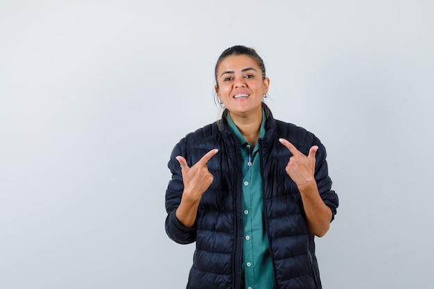 Jovem mulher apontando para si mesma em uma camisa, jaqueta e olhando alegre, vista frontal.