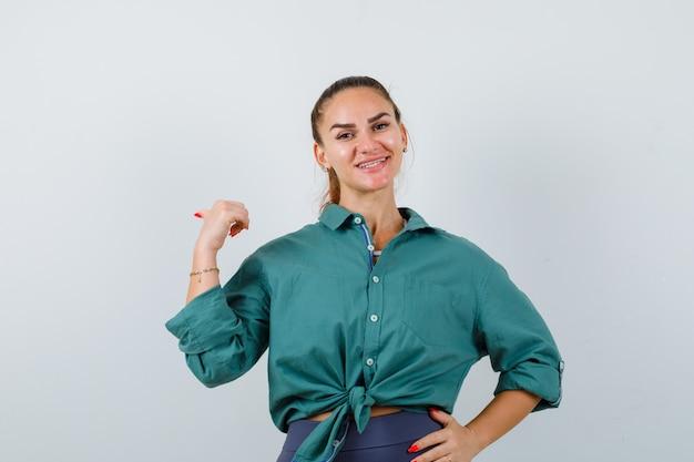 Jovem mulher apontando para trás com o polegar na camisa verde e olhando alegre, vista frontal.