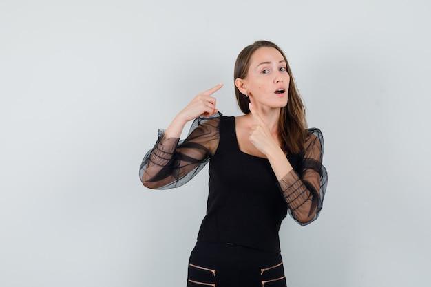 Jovem mulher apontando para uma orelha em blusa preta e calça preta e olhando com foco, vista frontal