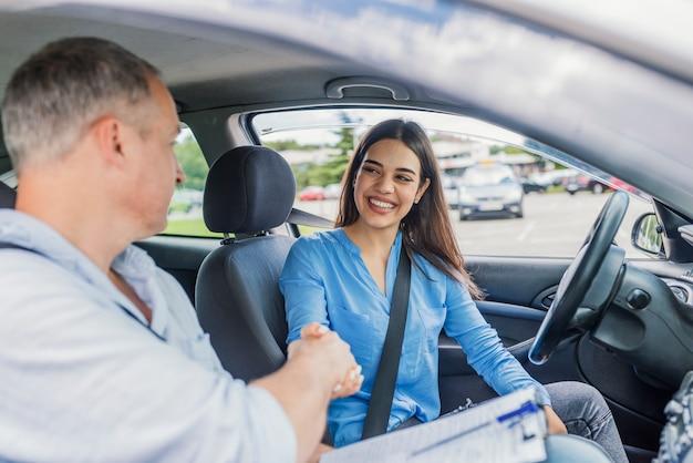 Jovem mulher aprendendo a dirigir carro junto com seu instrutor.