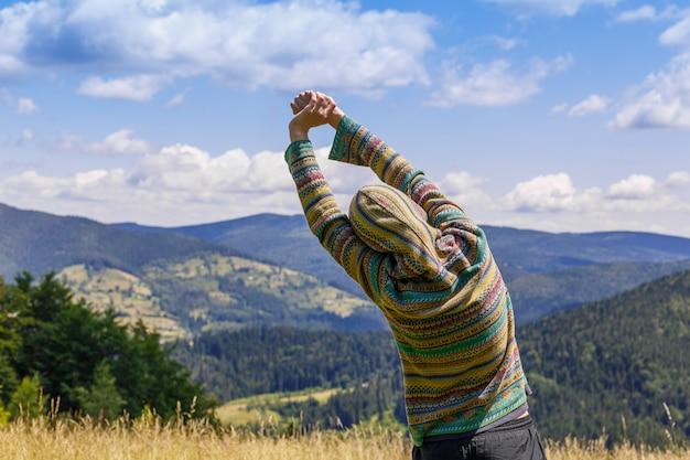 Jovem mulher apta que caminha nas montanhas que estão em uma crista rochosa do cume com trouxa e pólo que olha sobre uma paisagem alpina