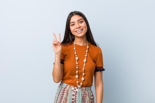 Jovem mulher árabe alegre e despreocupada, mostrando um símbolo de paz com os dedos.
