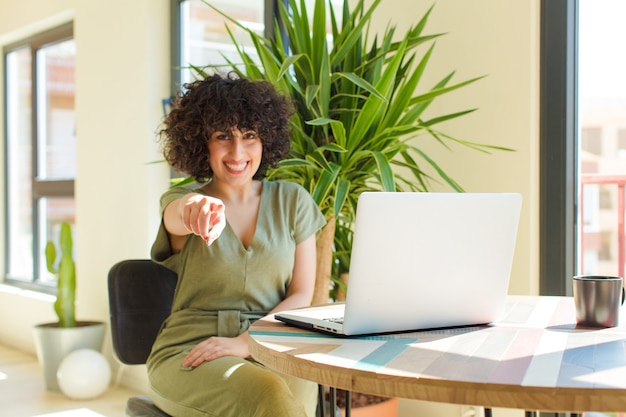 Jovem mulher árabe bonita com um laptop sobre uma mesa