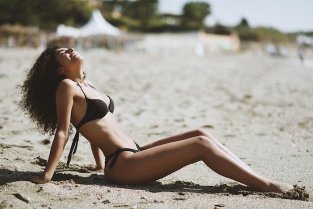 Jovem mulher árabe com corpo bonito em trajes de banho deitado na areia da praia
