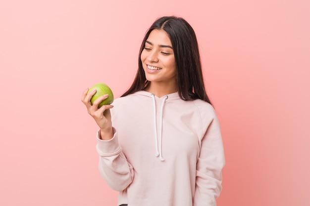 Jovem mulher árabe comendo uma maçã