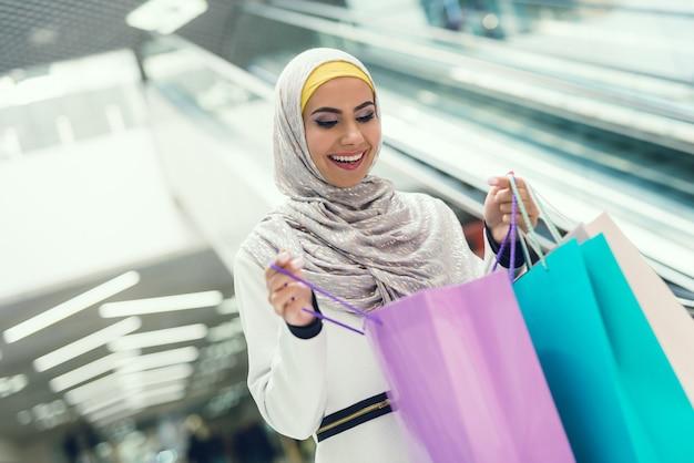 Jovem mulher árabe no cachecol está de pé perto da escada rolante.
