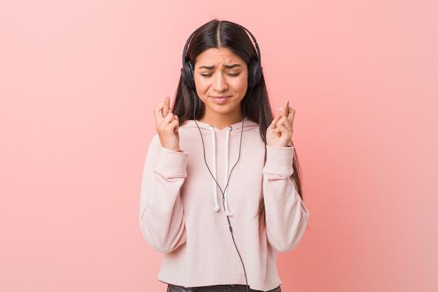 Jovem mulher árabe ouvindo música, cruzando os dedos por ter sorte