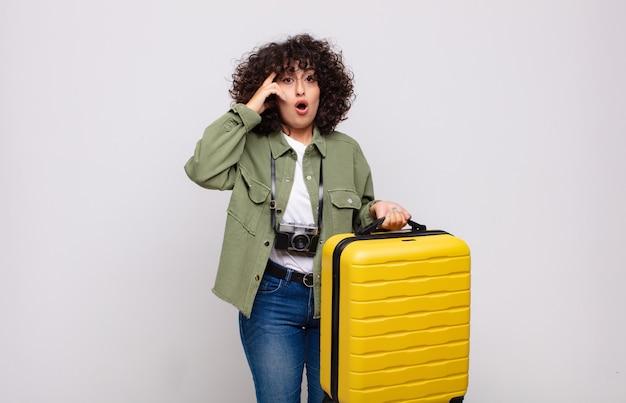 Jovem mulher árabe parecendo surpresa, boquiaberta, chocada ao perceber um novo pensamento, ideia ou conceito de viagem