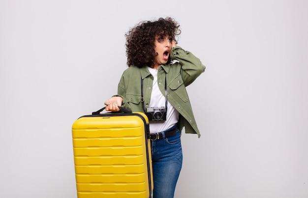 Jovem mulher árabe se sentindo feliz, animada e surpresa, olhando para o lado com as duas mãos no rosto, conceito de viagens