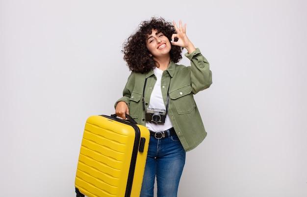 Jovem mulher árabe se sentindo feliz, relaxada e satisfeita, mostrando aprovação com um gesto de ok, sorrindo conceito de viagem
