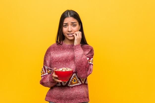 Jovem mulher árabe segurando as unhas roer uma tigela de cereal, nervoso e muito ansioso.