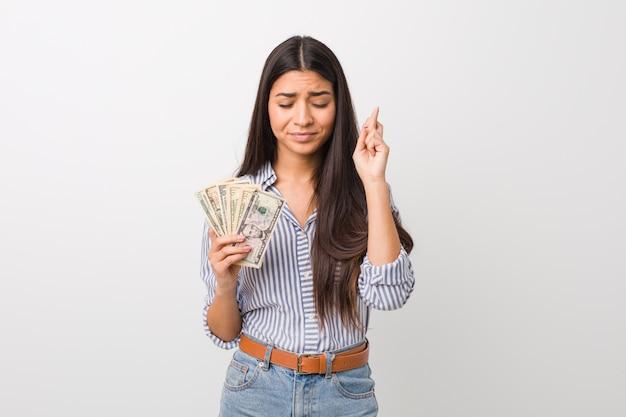 Jovem mulher árabe segurando dólares cruzando os dedos por ter sorte