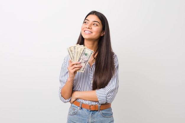 Jovem mulher árabe segurando dólares sorrindo confiante com braços cruzados.