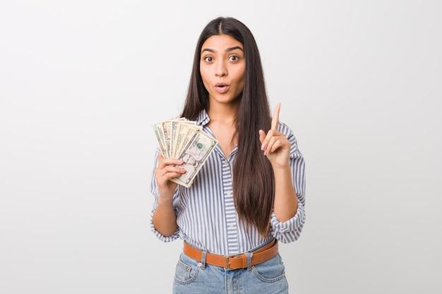 Jovem mulher árabe segurando dólares tendo uma ótima idéia, conceito de criatividade.