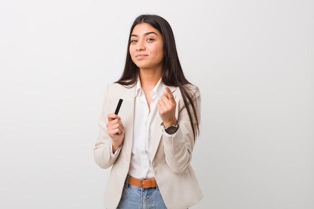 Jovem mulher árabe segurando um cartão de crédito, apontando com o dedo para você, como se estivesse convidando para se aproximar.