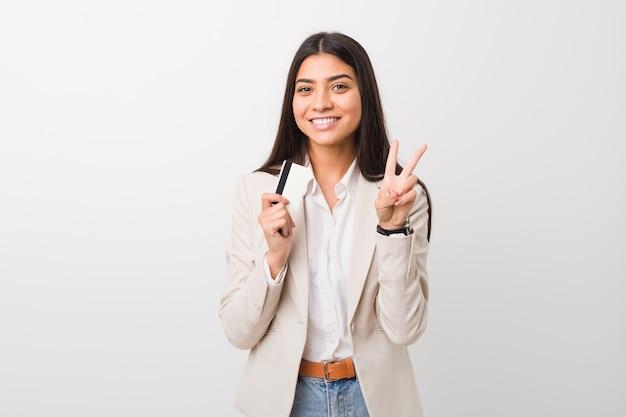 Jovem mulher árabe segurando um cartão de crédito, mostrando sinal de vitória e sorrindo amplamente.