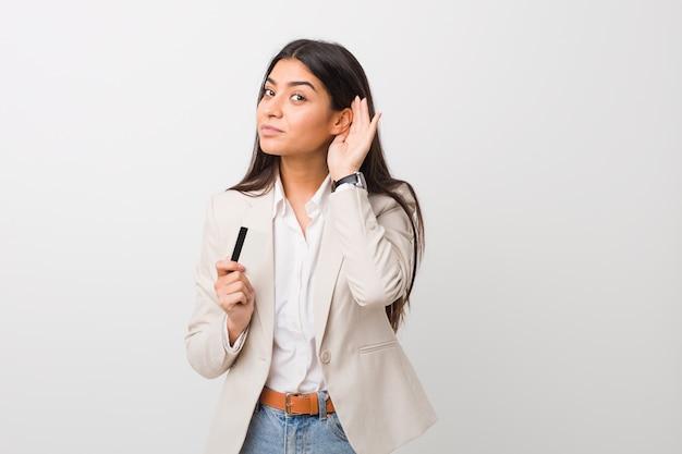 Jovem mulher árabe segurando um cartão de crédito, tentando ouvir uma fofoca.