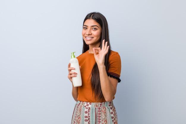 Jovem mulher árabe segurando um frasco de creme alegre e confiante mostrando o gesto de ok.