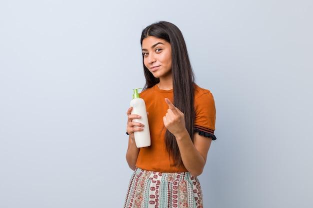 Jovem mulher árabe segurando um frasco de creme, apontando com o dedo para você, como se estivesse convidando para se aproximar.