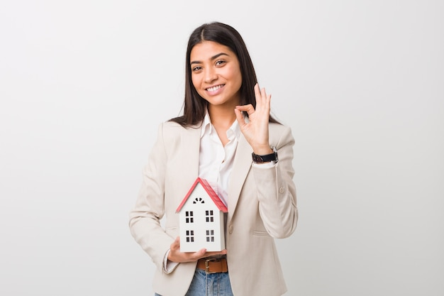 Jovem mulher árabe segurando um ícone de casa alegre e confiante, mostrando um gesto de ok.