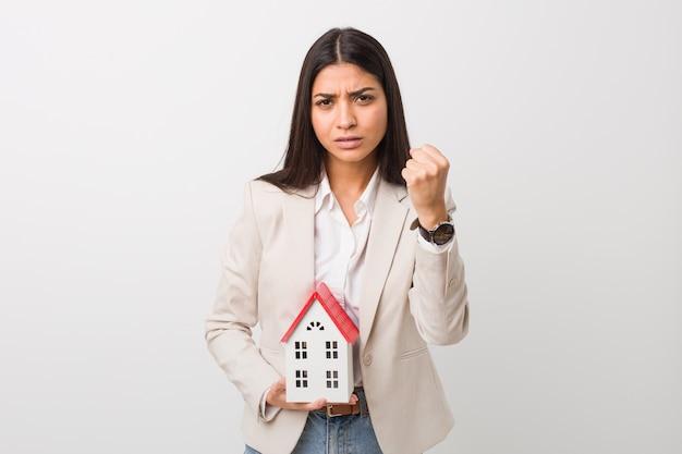 Jovem mulher árabe segurando um ícone de casa mostrando o punho para a câmera, expressão facial agressiva.