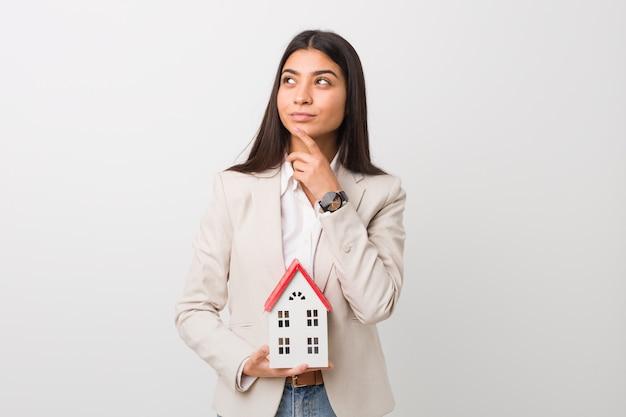 Jovem mulher árabe segurando um ícone de casa, olhando de soslaio com expressão duvidosa e cética.