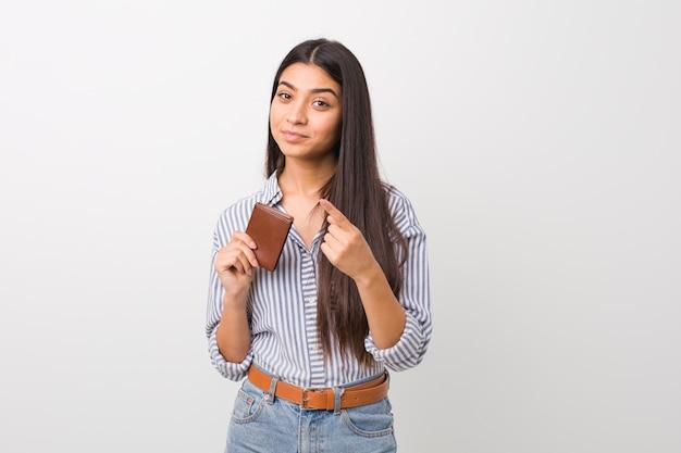 Jovem mulher árabe segurando uma carteira, apontando com o dedo para você, como se estivesse convidando para se aproximar.